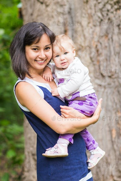 Mixed race happy mother with baby girl outdoors portrait