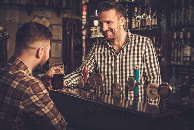 Man chatting with a bartender in a pub