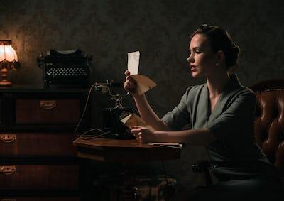 Beautiful woman reading letter in retro interior