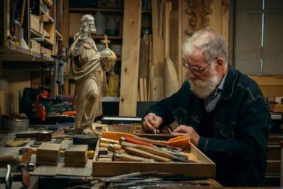 Senior wood carving professional during work