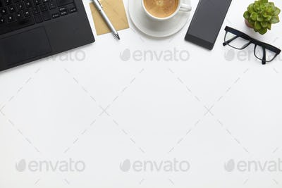 Laptop With Coffee Cup, Eyeglasses And Smartphone On White Desk