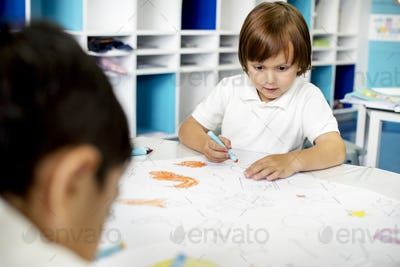 Group of diverse students coloring workbook in class