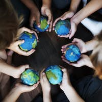 Group of diverse kids hands holding cupping globe balls together