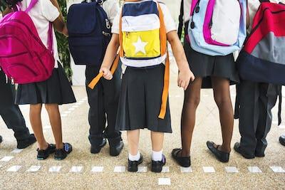 Group of diverse kindergarten students standing together in scho