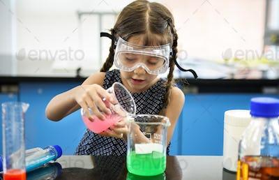 Kindergarten Student Mixing Solution in Science Experiment Labor