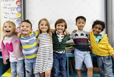 Group of diverse kindergarten students standing together in clas