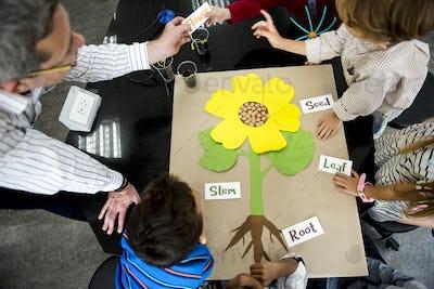 Teacher teaching flower structure to diverse group of kindergart