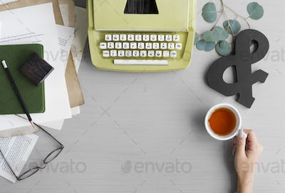 Retro Typewriter with Hand Holding Tea Cup on Gray Table