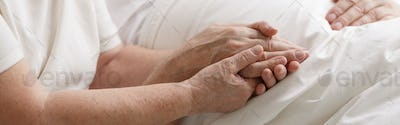 People holding hands in hospital