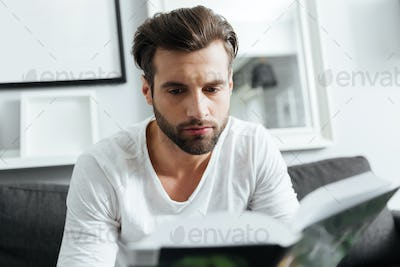 Concentrated man sitting on sofa reading book