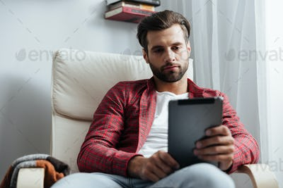 Serious young bearded man using tablet computer.