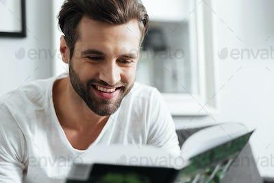 Smiling man reading book. Looking aside.