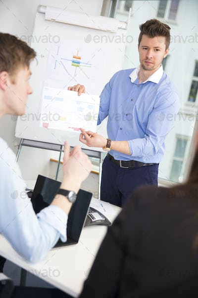 Confident Professional Showing Chart To Colleagues