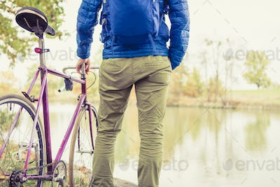 Man with road bike looking at river view in park