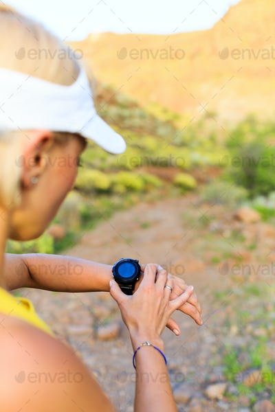 Runner checking sports watch in summer mountains on trail