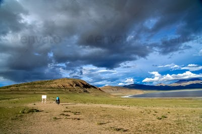 Solo female cyclist and tibetan lake