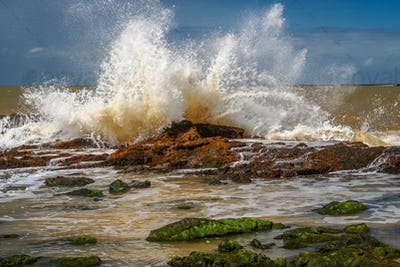 Strong wave hitting rocks on the beach