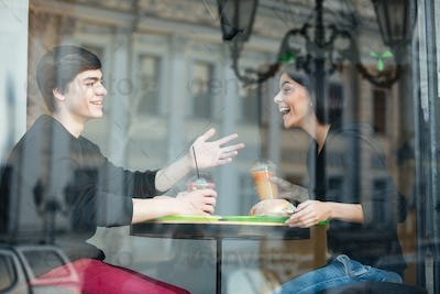 Smiling young man sitting in cafe with his sister drinking juice