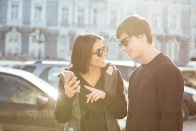 Cheerful young woman walking outdoors with brother using phone.