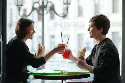 Happy young man sitting in cafe with sister drinking juice