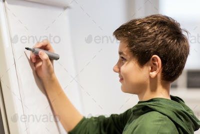 student boy with marker writing on flip board
