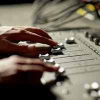 hands on mixing console in music recording studio