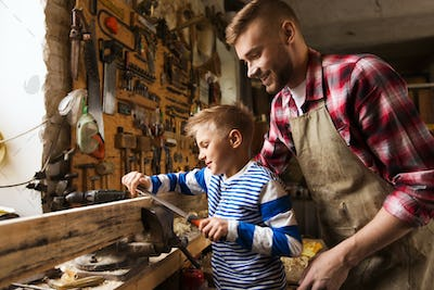 father and son with rasp working at workshop