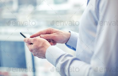 close up of man hands with smartphone at office