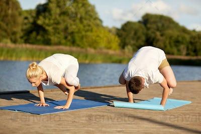 couple making yoga crow pose outdoors