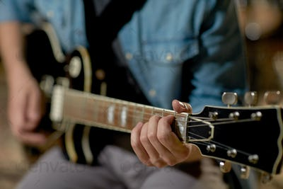 close up of man playing guitar at studio rehearsal