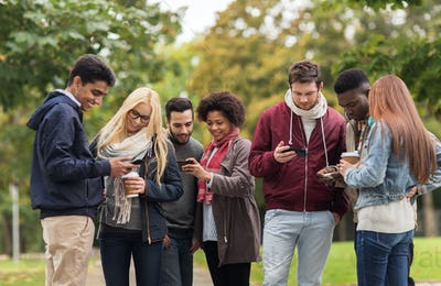 happy friends with smartphone and coffee outdoors