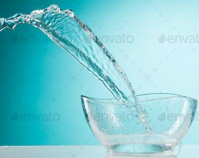 The water splashing to glass bowl on white background