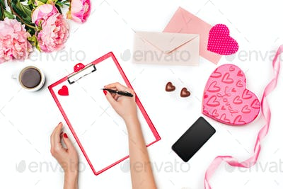The female hands with pen and gift box on white background