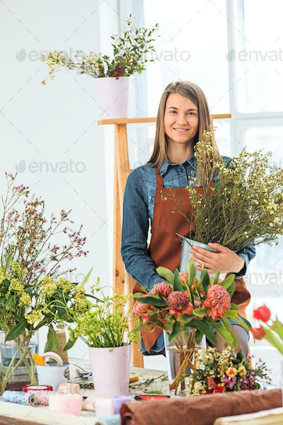 Florist at work: the young girl making fashion modern bouquet of different flowers