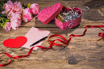 The gift box with hearts on wooden background