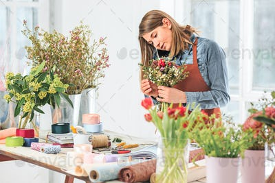 Florist at work: the female hands of woman making fashion modern bouquet of different flowers