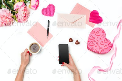 The female hands with phone and gift box on white background
