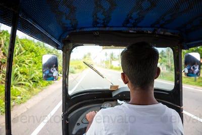 Tuk tuk driver on road of Sri Lanka, view from car