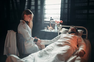 Female doctor measures the pulse of sick man