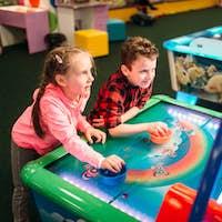 Little kids plays air hockey, entertainment center