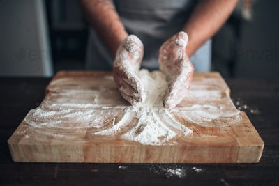 Male baker hands kneading dough on cutting board