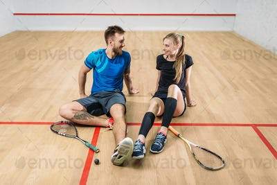 Squash game concept, young couple, rackets, ball