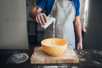 Male baker hands adds milk to the bowl
