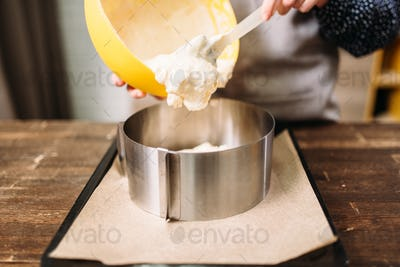 Woman cook adds cream for the cake into the pan