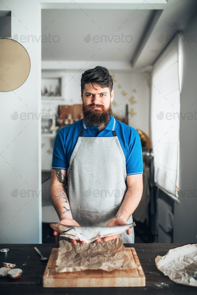 Chef hands holds raw fish over cutting board