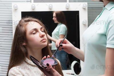 Make up artist applying make-up on girl face
