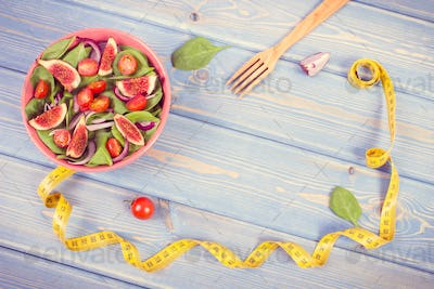 Vintage photo, Fruit and vegetable salad, fork with tape measure, copy space for text on boards