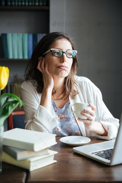 Pensive mature woman holding cup of tea and looking away