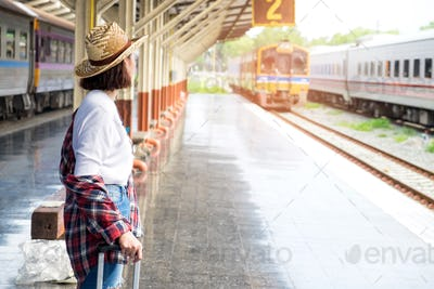 Female tourists are waiting for the train on the platform.
