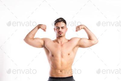 Shirtless fitness man flexing his arms. Studio shot.